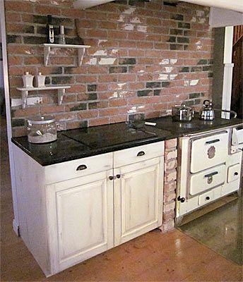 Vanha liesi ja täyspuinen JUVIn keittiökaappi sopivat oivallisesti yhteen. Rouhea tiiliseinä viimeistelee kokonaisuuden.