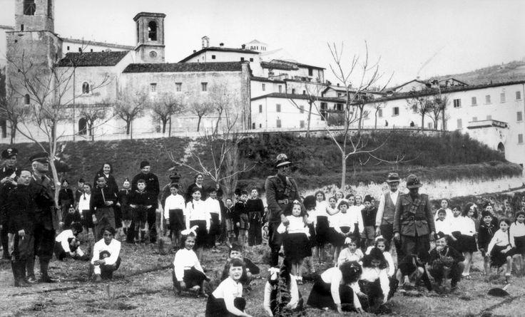 Cascia, anni 30. La festa degli alberi, la scolaresca del paese partecipa alla festa. Dietro la chiesa di San Francesco con il suo campanile e la torre civica.