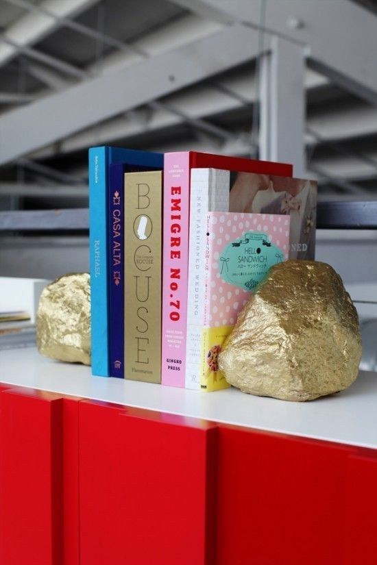 Ou, faça você mesmo alguns suportes de livros bem fáceis, pintando pedras com spray dourado.   54 maneiras de deixar seu cantinho do escritório mais agradável