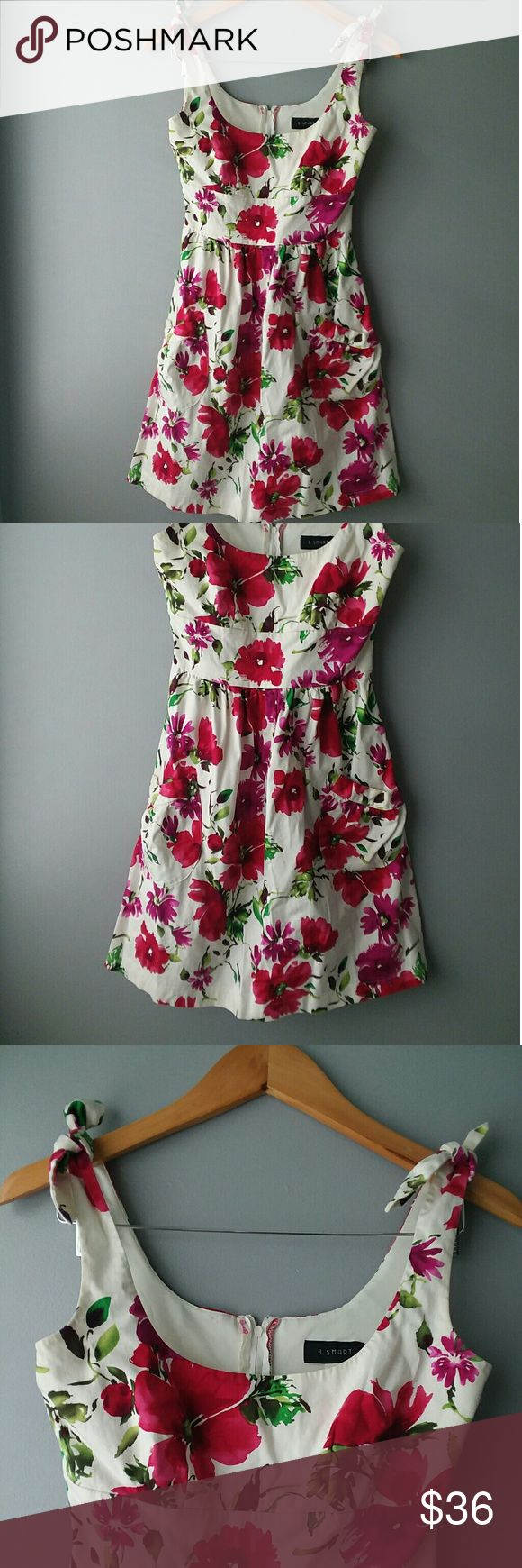 B. Smart floral dress red 2 front pockets Floral with 2 small front pockets. Purple, green, and red flower pattern.Great for spring or summer BBQs. Great condition. Sleeves tie. B. Smart Dresses Mini