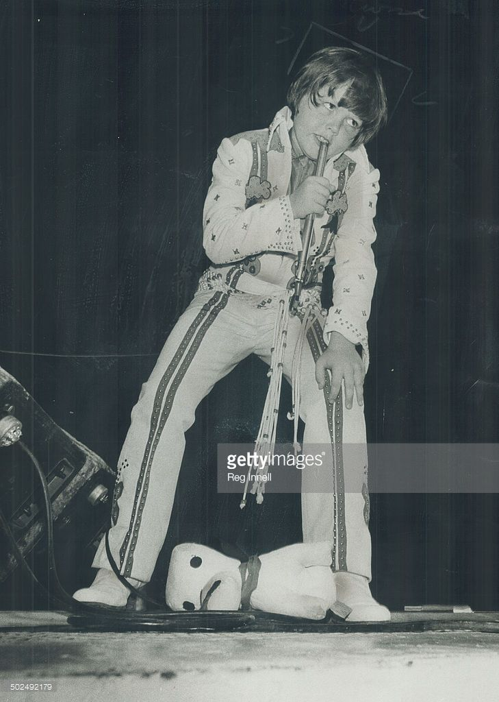 Eight-Year-old Jimmy; youngest of the Osmond Brothers; belts out some cradle rock last night at the CNE granstand. At his feet a stuffed toy dog thrown by the group's fans - hip-swinging pre-teen girls of the bubble-gaum set.