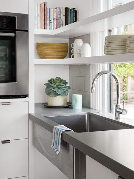 Beefy, painted plywood shelves cross in front of a window to add more storage without blocking views and reinforce the visual weight of solid-surface countertops.