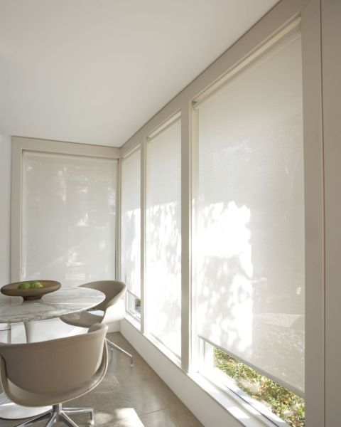 Light colors, a round table and roller shades instead of curtains make this room look bigger.   Solar Roller Shades - 13060