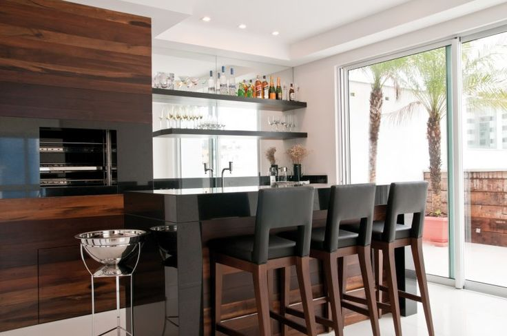 O jantar tem o apoio da bancada da churrasqueira, executada em granito preto absoluto. A madeira de demolição novamente foi a escolha para o revestimento da parede da bancada e do volume da churrasqueira.
