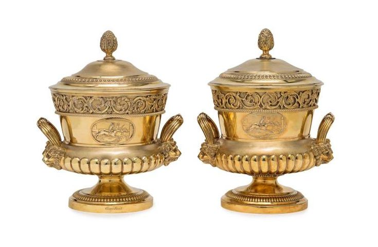 The Eglinton Race Cups, a grand George III pair of gilt sterling silver two handled urn shaped cup and covers by John Crouch, London 1810/1 each with a cast medallion depicting a horse race below a cast band of foliate scrolls, bold lion mask handles, domed cover with acanthus bud finial