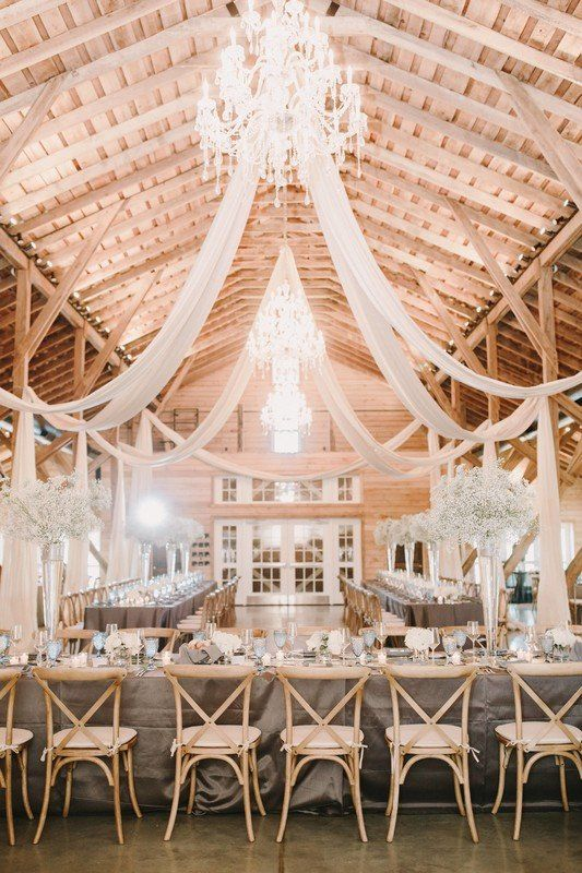 Barn wedding reception decor idea - barn venue with chandeliers, draped fabric + gray table linens  {Hunter & Company Event Planning and Design}