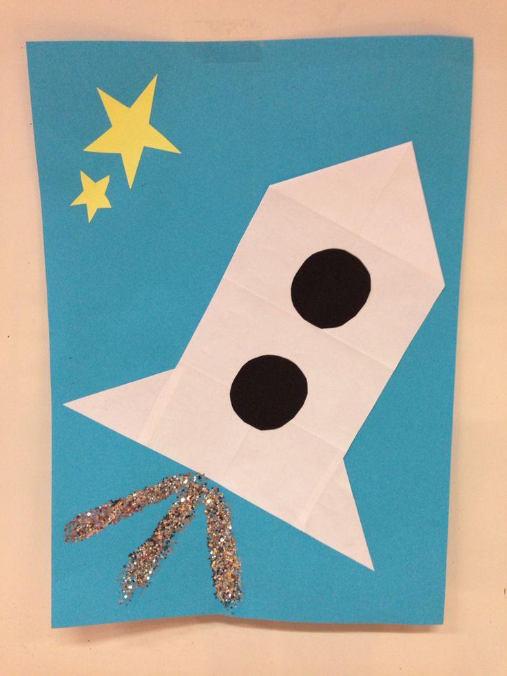 Raket vouwen - thema Ruimte: 16 vierkantjes vouwen, buitenste randen afknippen. Van de rand die is afgeknipt haal je 1 vierkantje af. Daar knip je twee driehoekjes van en die plak je aan het raketje vast.