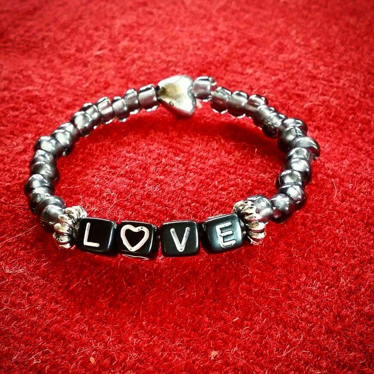 Armband med text love. Grå akrylpärlor, hjärta och mellandelar i metall. Pris 55 kr inkl port.