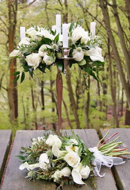 Florissimo, Shropshire. Elevated wedding table-centres are so elegant. Plus, they allow your guests to be able to chat to each other across the table, as the flowers are above eye-level. Here we have white roses, calla lilies, ranunculus and eryngium thistle.