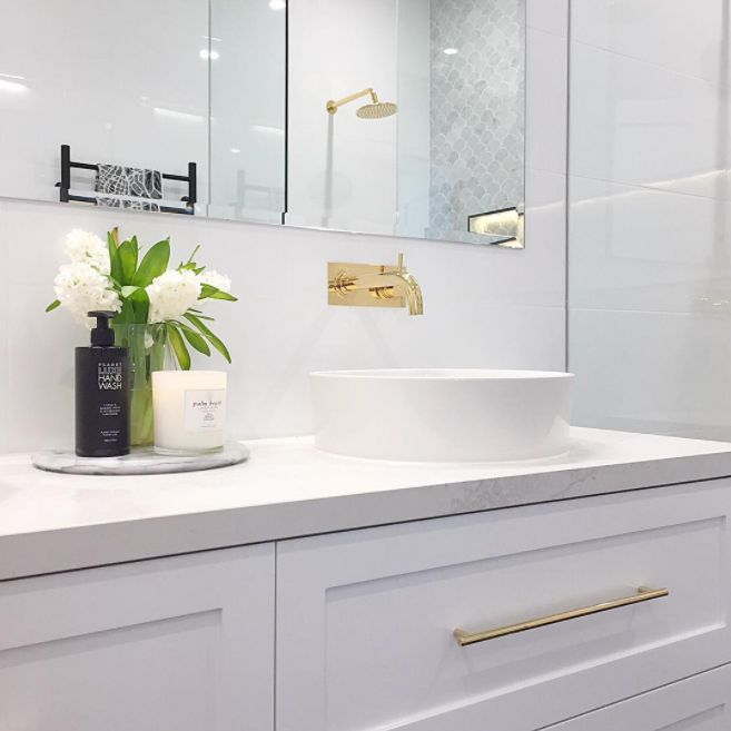 Incredibly beautiful and feminine bathroom with Shaker style vanity drawers, brass pull handles and brass tapware, and stone-look vanity top. The fish scale marble mosaic wall in the shower is also to die for! Go to the blog now by clicking on the image to see even more photos!
