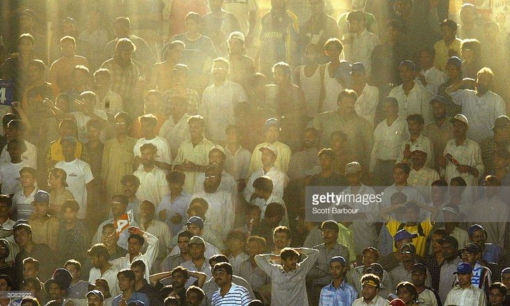 Cricket fans watch the final over of the match as the sun shines through the stand during the first Pakistan v India one day international match played at the National Stadium March 13, 2004 in Karachi, Pakistan. It is the Indian teams first full tour of Pakistan in almost 15 years, comprising five one-day internationals followed by three Tests. The tour is seen as evidence that the two nuclear-armed rivals are getting closer after almost going to war over the Himalayan region of Kashmir…