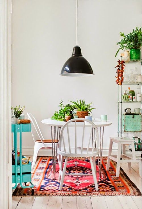 Great urban jungle dinging room with a white table, a turquoise bar cart and a black pendant light.