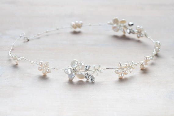 A long bridal hair garland with flower details made up of freshwater pearls, creamy keshi pearls and super-sparkly Swarovski crystal leaves. Worn around the head, across the forehead or even plaited through the hair, this pretty piece is so versatile and works with a range of different looks. All Kate & The Crown pieces are hand made in the UK for each recipient so please get in touch if you have any bespoke requirements.