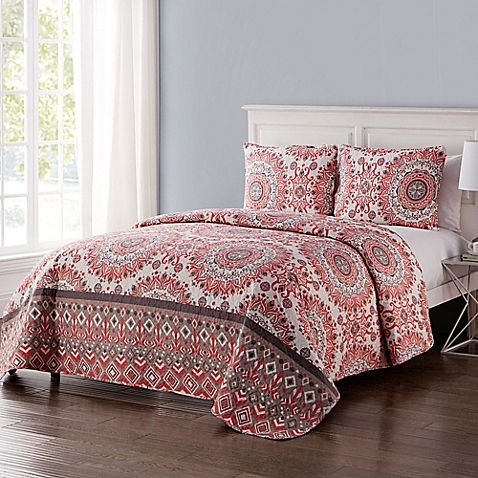 Brighten your bedroom with the bold, feminine VCNY Home Phoebe Reversible Quilt Set. Beautifully embellished with a complex circular pattern in warm coral colors, the ornate bedding is a lively addition to any bedroom.