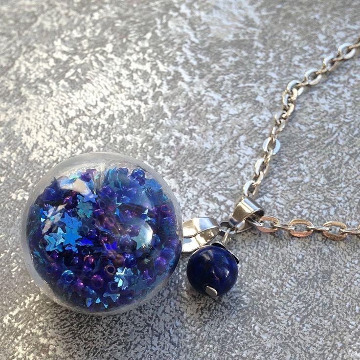 Noční+obloha+v+kouli+Skleněná+koule+naplněná+modrým+drobným+rokajlem+a+hvězdičkami.+Velikost+koule+2,5+cm.+Přívěsek+je+doplněn+kuličkou+lapisu+lazuli.+Řetízek+v+barvě+oceli+-+běžný+kov,+zapínání+karabinka+a+délka+70+cm
