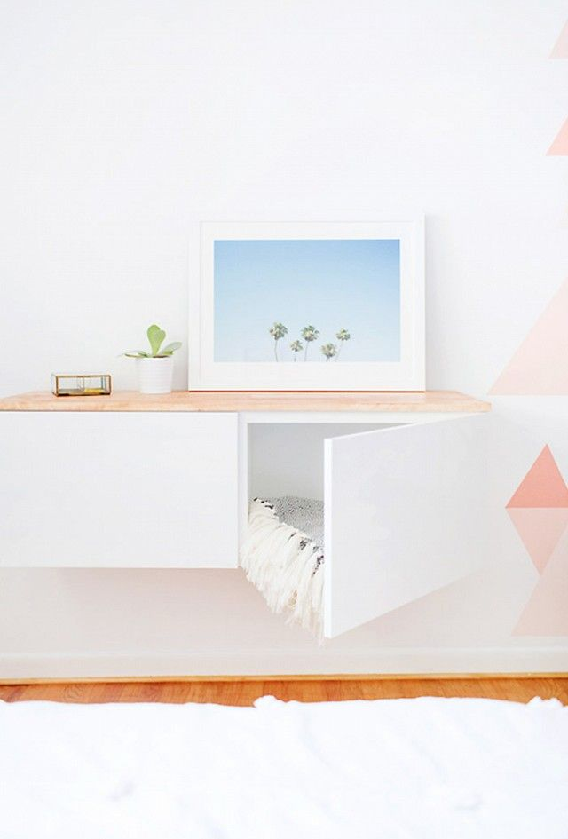 By hanging IKEA's Bestå shelf unit on the wall and topping it with a stained panel of wood, one decorating created a floated credenza that looks way more costly than it is.