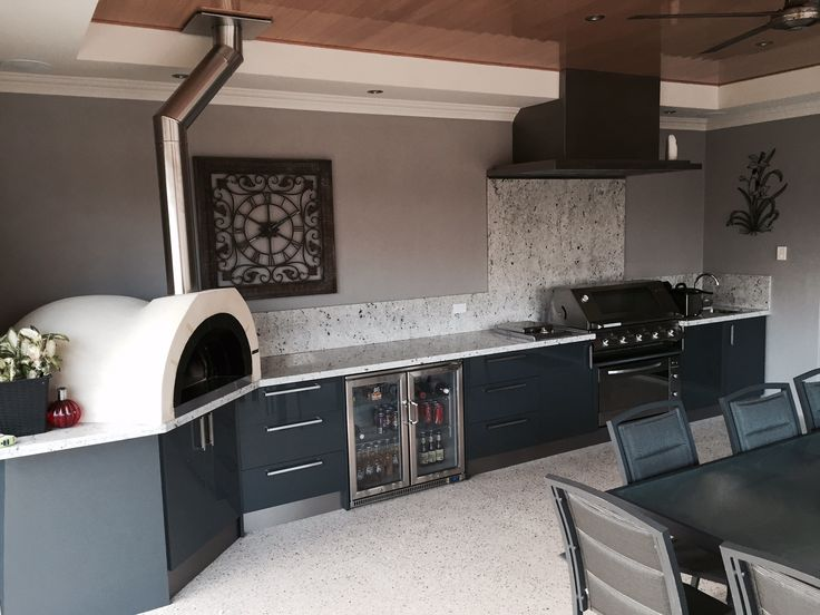 Alfresco kitchen with Eleganz perspex doors, wood fired pizza oven, Romano White granite and under bench oven