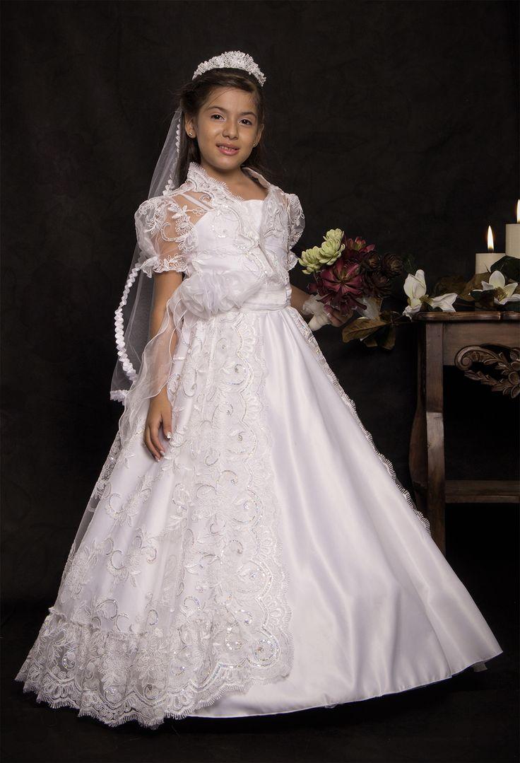REF.14-44 Vestido de primera comunión entero con manga sisa, lleva un cinturón con un penacho y con falda de encajes. Adicionalmente trae un chaleco con bordados el cual le da un toque diferente y tierno al vestido. Incluye corona y velo.