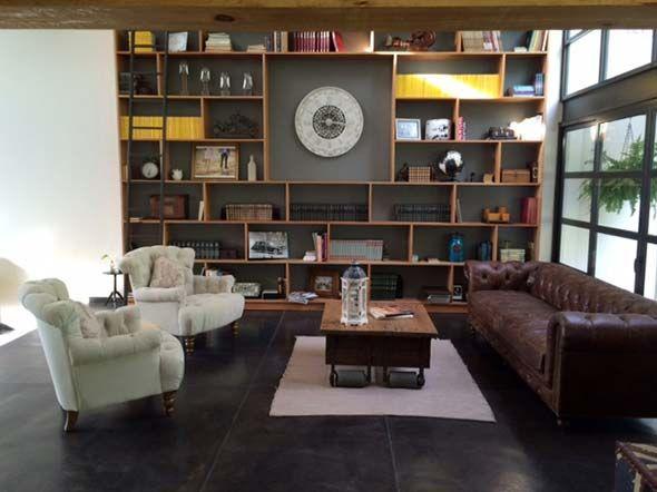 ¡Librero de toda la pared! En los estudios que son bastante espaciosos, se ven increíble los libreros grandes. En este depa amueblado por Nomada Studio, el librero, al albarcar toda la pared, se convierte en el foco de atención del espacio. Además, las repisas irregulares dan un estilo ecléctico a la pared, así como la combinación de distintos objetos como cuadros, libros o recuerdos. Dejar un espacio grande en el centro es una buena idea para disminuir la saturación de la pared.