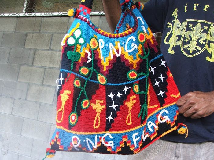 A colorful Papua New Guinea (PNG) 'bilum' - a traditional Highlands wool-woven bag. Today you can find 'bilums' in a variety of colours. This one has a series of PNG flags on it. #PapuaNewGuinea