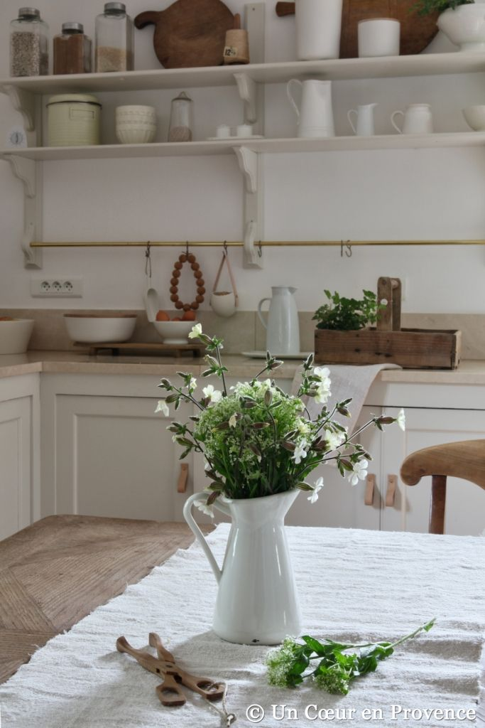 White kitchen with natural wood colour, bunch of white field flowers in a 'Ikea' jug love the feel of the kitchen