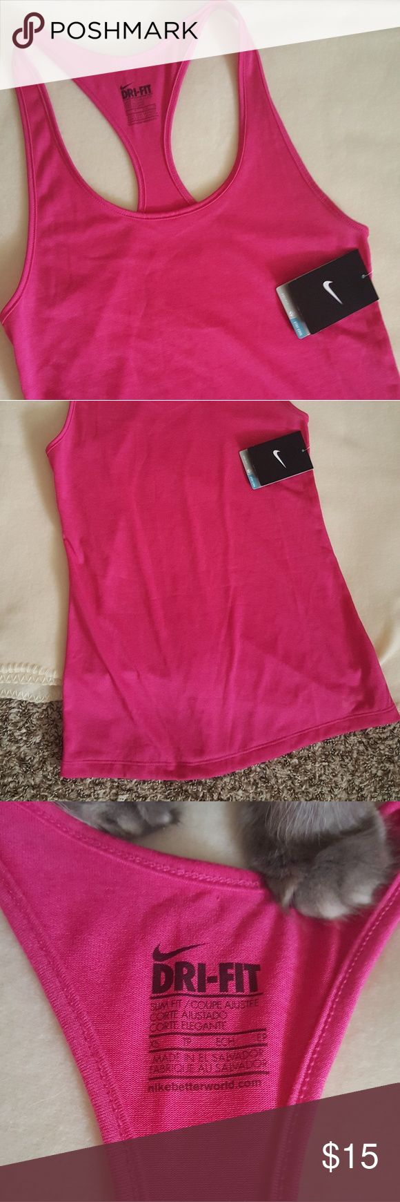 NWT Nike tank top NWT Nike dri-fit racer back tank top. Hot pink. Slim fit. Purchased the wrong size and didn't realize it was a slim fit. Yes, that is my cat's paw. He didnt actually get on the shirt.   Smoke free home  Reasonable offers considered and usually accepted No trades  Bundle and save! Nike Tops Tank Tops