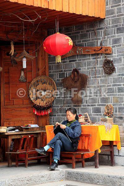 Woman knitting in a souvenir shop, Fenghuang Town, Hunan, China