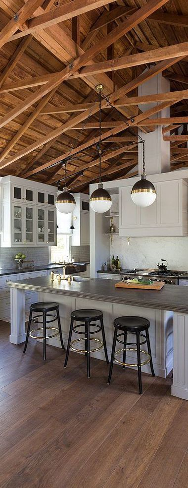 Fabulous kitchen features a truss ceiling accented with three small Hicks pendants illuminating a pale gray center island. Brass accents create warmth.