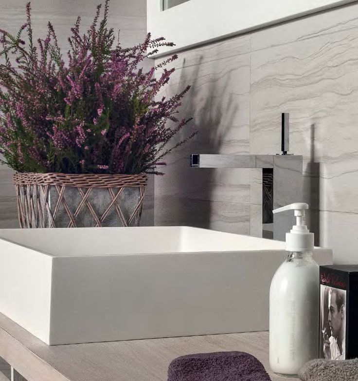 Modern white sink is accentuated well against the back drop of the calcareous streaks in silver.