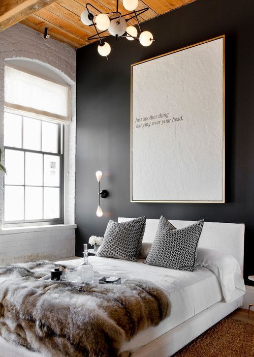 Dark bedroom walls with oversized typography canvas.