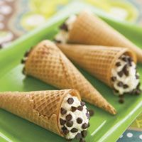 Cannoli Fake-Out!        3 cup(s) (whole-milk) ricotta cheese      zest of 1 orange      1/4 cup(s) (superfine) sugar, use regular sugar if unavailable      8  sugar cones      1 cup(s) mini chocolate chips      1/2 cup(s) confectioners' sugar, in a sieve or sugar shaker