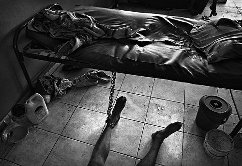 Jan Dago > The patients at The Sierra Leone Psychiatric Hospital are often chained in order to not escape or hurt the other patients. The dark bucket under the bed is used as a toilet