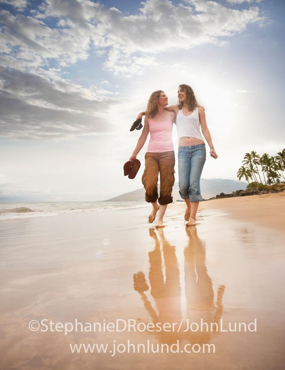 Picture of a mother and her adult (teen aged) daughter engaged in conversation as they walk along a tropcial beach in intimate friendship.