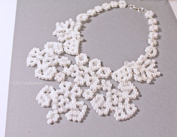 Inspired by maple leaves, hierarchies, and the majestic great white North, this statement wedding necklace is made from hundreds of white and clear perler/hama beads. Perfect for overlaying on a simple dress, or a beautiful wow moment on a strapless gown. This piece took 3 hours to make, and is actually 26 separate sections combined. Also, because the beads themselves are ironed together, if the piece falls apart you are able to re-iron it back together! And if a particular color bead p...