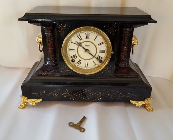 """Antique mantle clock with lion head décor and faux marble finish over wood cabinet, circa late 1800's, 15""""Lx6.5""""Dx10.5""""H with brass key."""