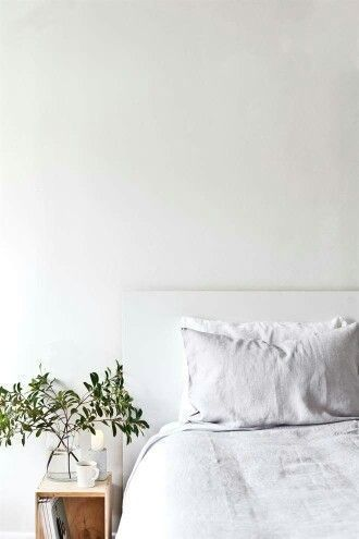 A light, white bedroom, add a touch of calm and greenery with plants by the bed