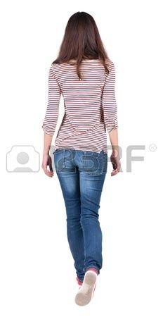 Vista posterior de la mujer que camina con jeans hermosa chica morena en movimiento trasero vista de Foto de archivo