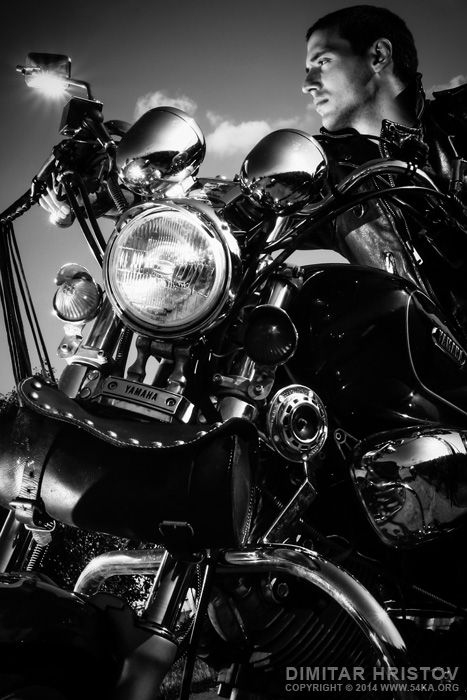 Biker riding a customized motorcycle Photo young wheel wear view velocity vehicle travel transportation transport sky sitting rider Ride posing pose person outside outdoors motorcycle motorbike motor man male machine guy driver drive chopper blue black and white biker bike