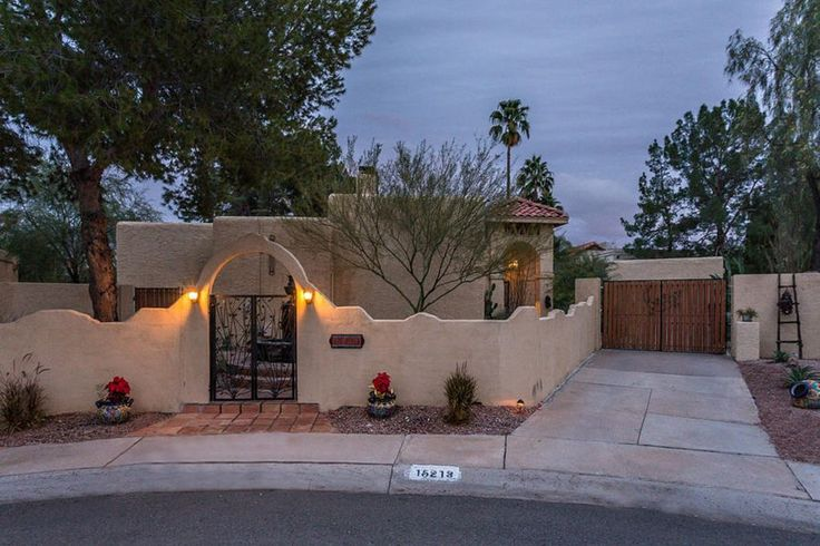 Southwestern Exterior of Home with exterior stone floors, Pathway, Gate, Fence