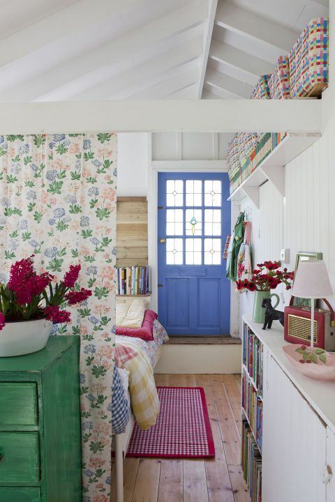 Offset a white background with block color by using a thoughtful palette of bright shades that will draw your eye to certain design elements. Here, the door has been turned into a focal point using a blue paint, while a red gingham rug, multicolored woven baskets and a chest of drawers painted in a vivid green all reflect the tones seen in the patterned curtain. This creates a cohesive yet distinctive style in a room with an open floor plan. Click through for more ways to make your home feel…
