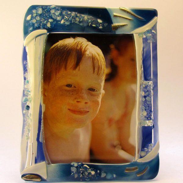 """Portafoto """"Elegant"""" (PT09) è una cornice elegante ed importante, adatta ad incorniciare una foto speciale. Il tris dei differenti blu e turchese, delle lastre opalescenti, donano risalto al bianco, alle graniglie di vetro trasparente e ai punti luce color argento."""