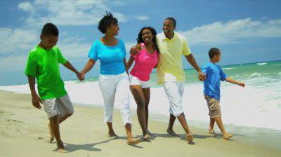 African American family enjoying summer vacation walking ...