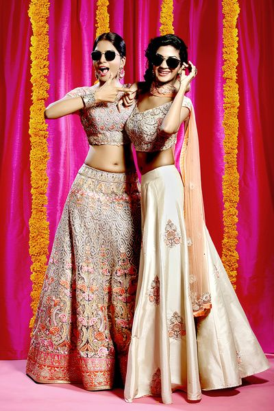 Sister of the Bride - Bride in a Beautiful Dull Gold Lehenga with Multi-colored Embroidery and the Sister in a Plain Gold Lehenga with Scattered Motifs | WedMeGood #wedmegood #gold #sisterofthebride #indianbride #indianwedding #lehenga #bridal