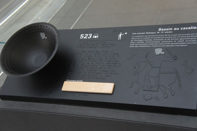 Tactile representation of an exhibit and braille description at a museum.