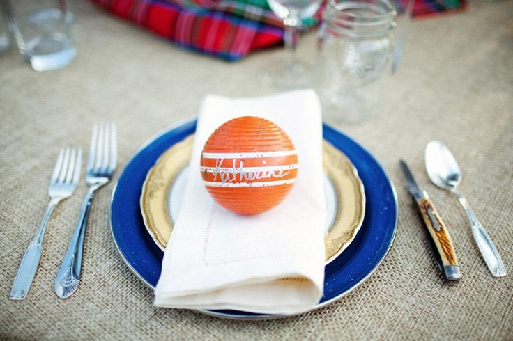 A preppy party table setting with a (faux?) burlap tablecloth, simply folded napkin and a croquet ball that doubles as a place card.