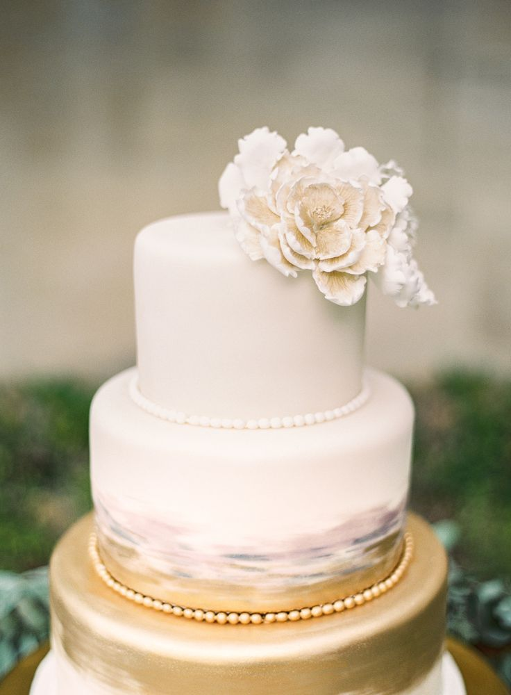 sophisticated fold and watercolor wedding cake with pearling and an icing flower topper | Photography: Sposto Photography