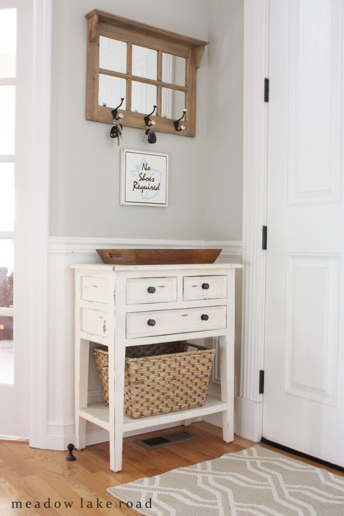 Small entry table with mirror and key hooks above. www.meadowlakeroad.com