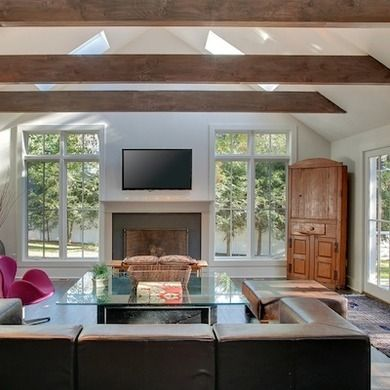 The room is made even more dramatic by its cathedral ceiling, wood beams, and natural light—from above and all three sides.