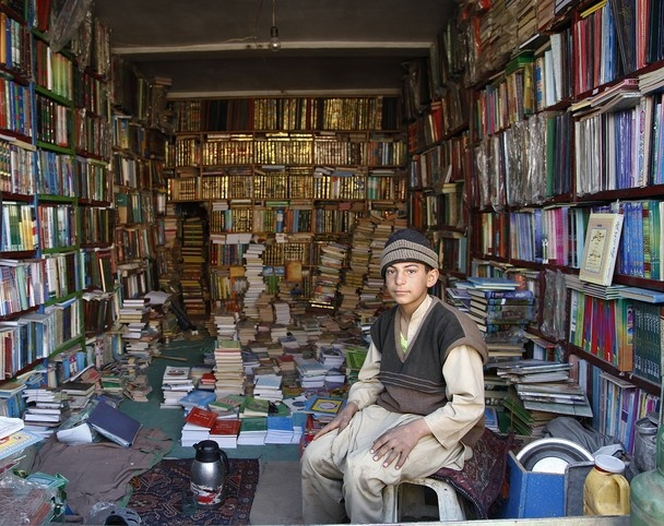 A young boy who works selling second-hand books in an improvised place for his parents. This image was captured in Herat, March 2013.  (From National Geographic)