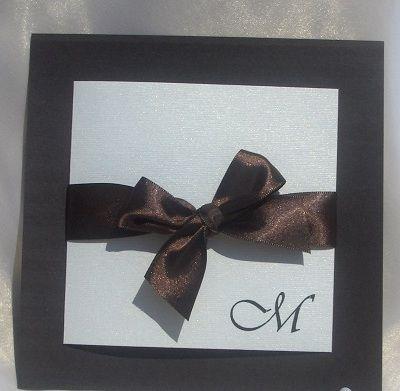 "Invitatie nunta ""Hot Chocolate"" realizata din cartoane sidefate maro si ivoire si accesorizata cu o panglica maro. Pe coperta invitatiei sunt imprimate initialele numelor celor doi miri. Invitatia ..."